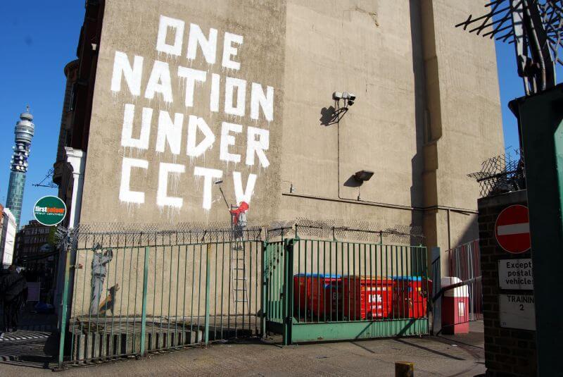 bansky mural against cctv